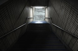 Empty dark underpass perspective. Stone stairs go down to the light. Abstract night city background