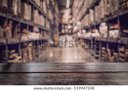 Empty dark wood table top on blurred warehouse background for  display your products.