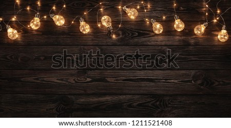 Empty, dark wooden background illuminated by retro light bulbs, with copy space  #1211521408