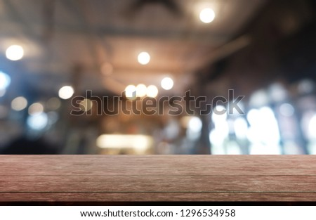 Empty dark wooden table in front of abstract blurred background of restaurant, cafe and coffee shop interior. can be used for display or montage your products - Image #1296534958