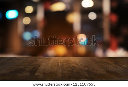 Empty dark wooden table in front of abstract blurred bokeh background of restaurant . can be used for display or montage your products.Mock up for space #1231109653