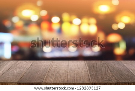 Empty dark wooden table in front of abstract blurred bokeh background of restaurant . can be used for display or montage your products.Mock up for space #1282893127