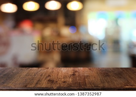 Empty dark wooden table in front of abstract blurred bokeh background of restaurant . can be used for display or montage your products.Mock up for space. #1387352987