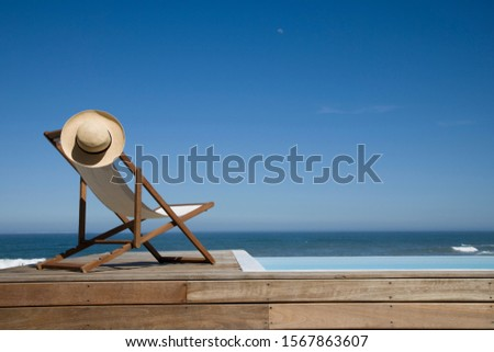 Empty deck chair near swimming pool
