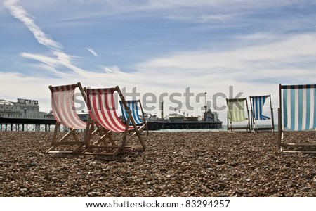 Empty deck chairs on Brighton beach with the pier in the background - stock photo