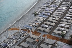Empty deck chairs with mattresses and umbrellas on a pebble beach on Mediterranean sea coast in summer