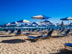 Empty deckchairs and parasols on empty beach
