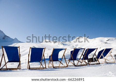 Empty deckchairs in front of ski slopes in alps mountains