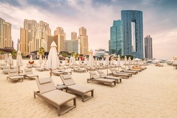 Empty deckchairs with umbrellas and sunbeds at the JBR beach in Dubai. Travel and vacation destinations in United Arab Emirates