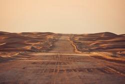 Empty desert road in the middle sand dunes. Abu Dhabi, United Arab Emirates