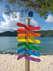 Empty direction road colorful wooden signs with sand beach, turquoise waters and sky on background. Funny signpost with empty space for writing.