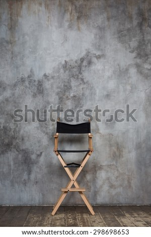 Empty directors chair against grungy wall