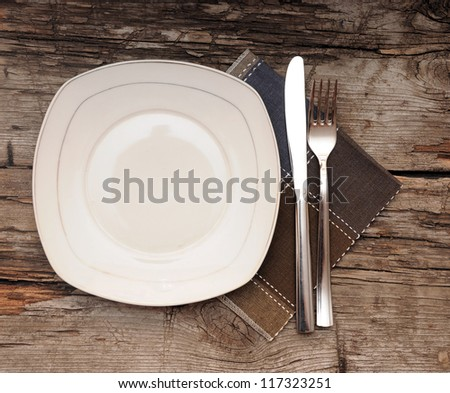 Empty dish, knife and fork and brown napkin on old wood table