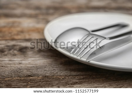 Empty dishware and cutlery on wooden table, close up view. Table setting #1152577199