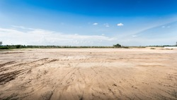 Empty dry cracked swamp reclamation soil, land plot for housing construction project with car tire print in rural area and beautiful blue sky with fresh air Land for sales landscape concept.