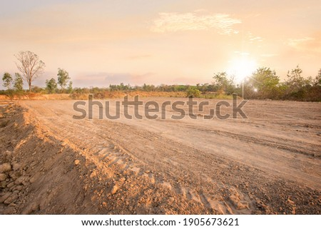 Empty dry cracked swamp reclamation soil, land plot for housing construction project with car tire print in rural area and beautiful sun set with fresh air Land for sales landscape concept Stockfoto ©