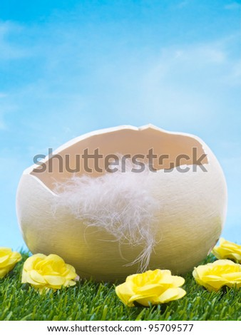 Empty easter egg in grass with flowers on sky background