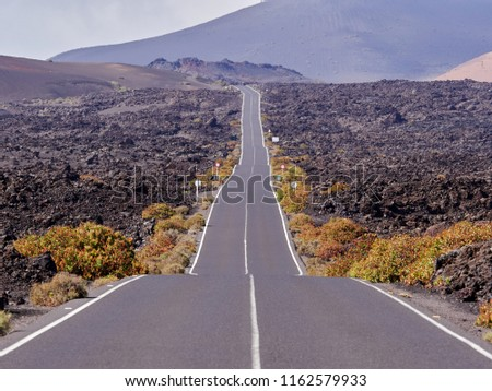 Empty endless highway through the volcanic landscape of Lanzarote island, Canary islands, Spain #1162579933