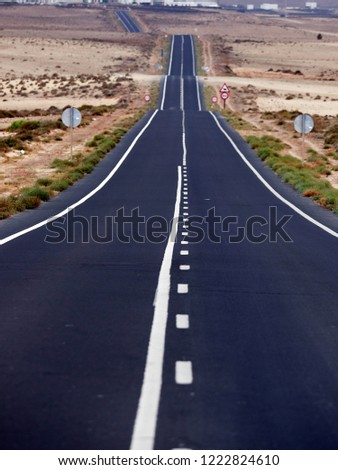 Empty endless highway through the volcanic landscape of Lanzarote island, Canary islands, Spain #1222824610