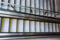 empty Escalator and stairs separated by glass railings in underpass. Modern Transportation, Urban infrastructure. Pandemic-stricken urbanism, empty city in covid era, lockdown, quarantine. no people