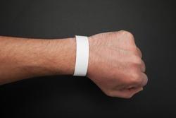 Empty event ticket wrist band design. Concert blank paper wristband, bracelet mockup on black background.