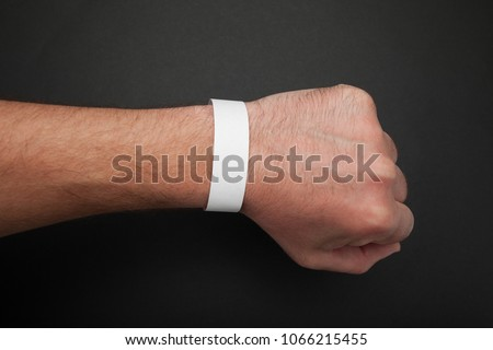 Empty event ticket wrist band design. Concert blank paper wristband, bracelet mockup on black background. #1066215455