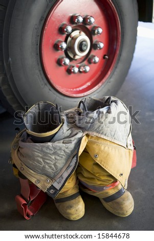 Empty firefighter's boots and uniform next to fire engine