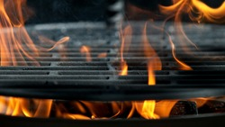Empty flaming cast iron grate charcoal grill with open fire, ready for product placement.