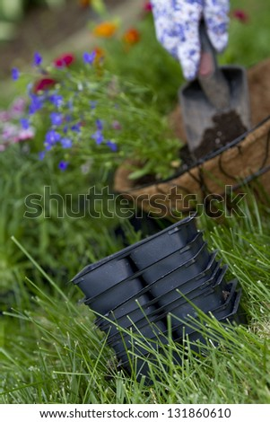 empty flower containers focus on empty flower containers. gardener has planted flowers in coco wire basket in background out of focus.