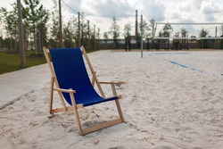 Empty folding deckchair on the edge of the beach volleyball court.