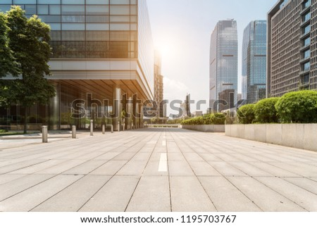 empty footpath with modern office building exterior and blue cloudy sky during sunrise