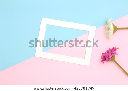 Empty frame and flowers flat lay on blue and pink pastel background with copy space. Soft effect filter.