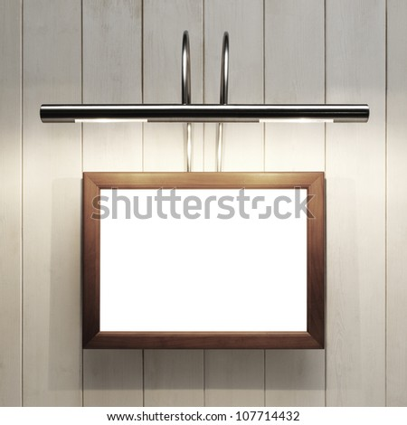 Empty frame on wooden wall with lamp