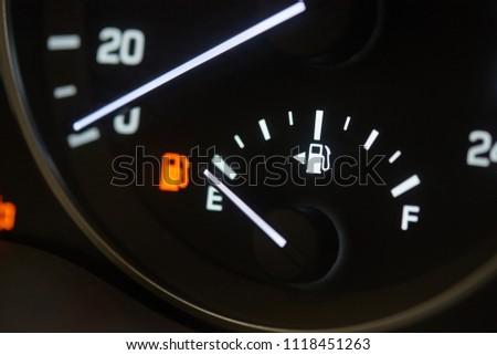 Empty fuel tank indicator close-up on modern car dashboard.