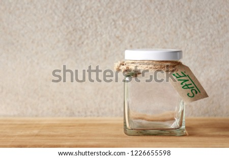 Empty glass bottle with save wording on paper tag, for saving money in daily life, saved for good lifestyle concept #1226655598