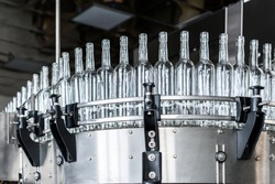 Empty glass bottles on the conveyor. Factory for bottling alcoholic beverages.