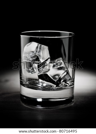 Empty glass filled with ice cubes; black and white