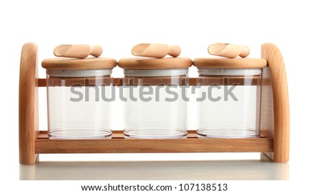 empty glass jars for spices with spoons on wooden shelf isolated on white