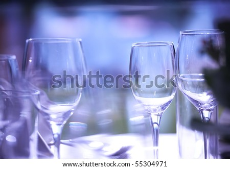 Empty glasses on restaurant table lit with purple light