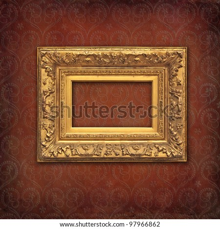 Empty golden frame on a Victorian grunge red damask wallpaper
