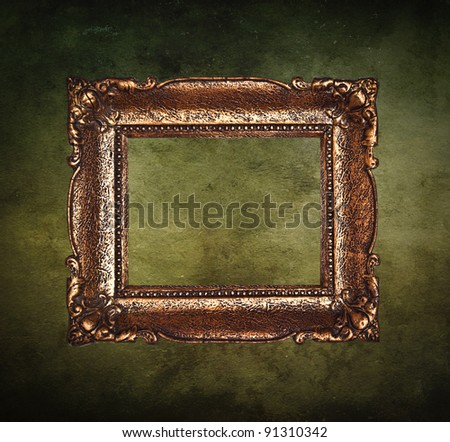 Empty golden frame on grunge wall - stock photo