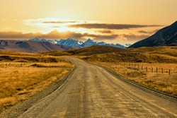 Empty gravel dirt road winding through the rural countryside of Hakatere Conservation park in the Ashburton highlands with a backdrop of the Southern Alps