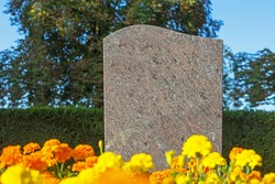 Empty gray granite gravestone on  blue sky, yellow flowers, green tree background, text place