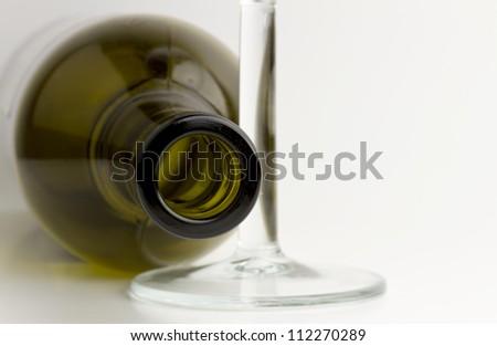 Empty green glass wine bottle with stem wineglass.