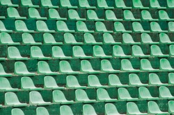 Empty green plastic spectators seats closeup on tennis court stand