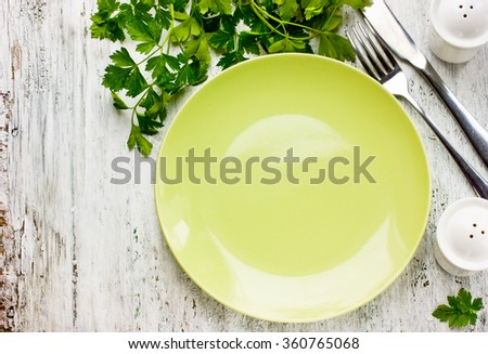 Empty green plate and fresh parsley on rustic white wooden background, place for text