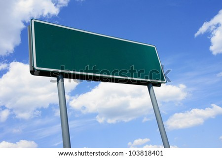 Empty green road sign against blue sky with clouds - a place for your own text on a green sign.