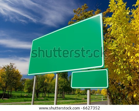 Empty green signboard at the roadside in an autumn landscape. Add your own text
