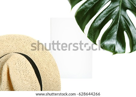 Empty greeting card mock up with straw hat and leaf of tropical palm leaf isolated on white background top view. Minimal styled feminine desktop. #628644266