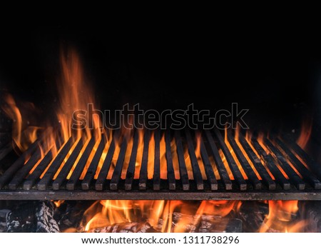 Empty grill grate and tongues of fire flame. Barbeque night background.
